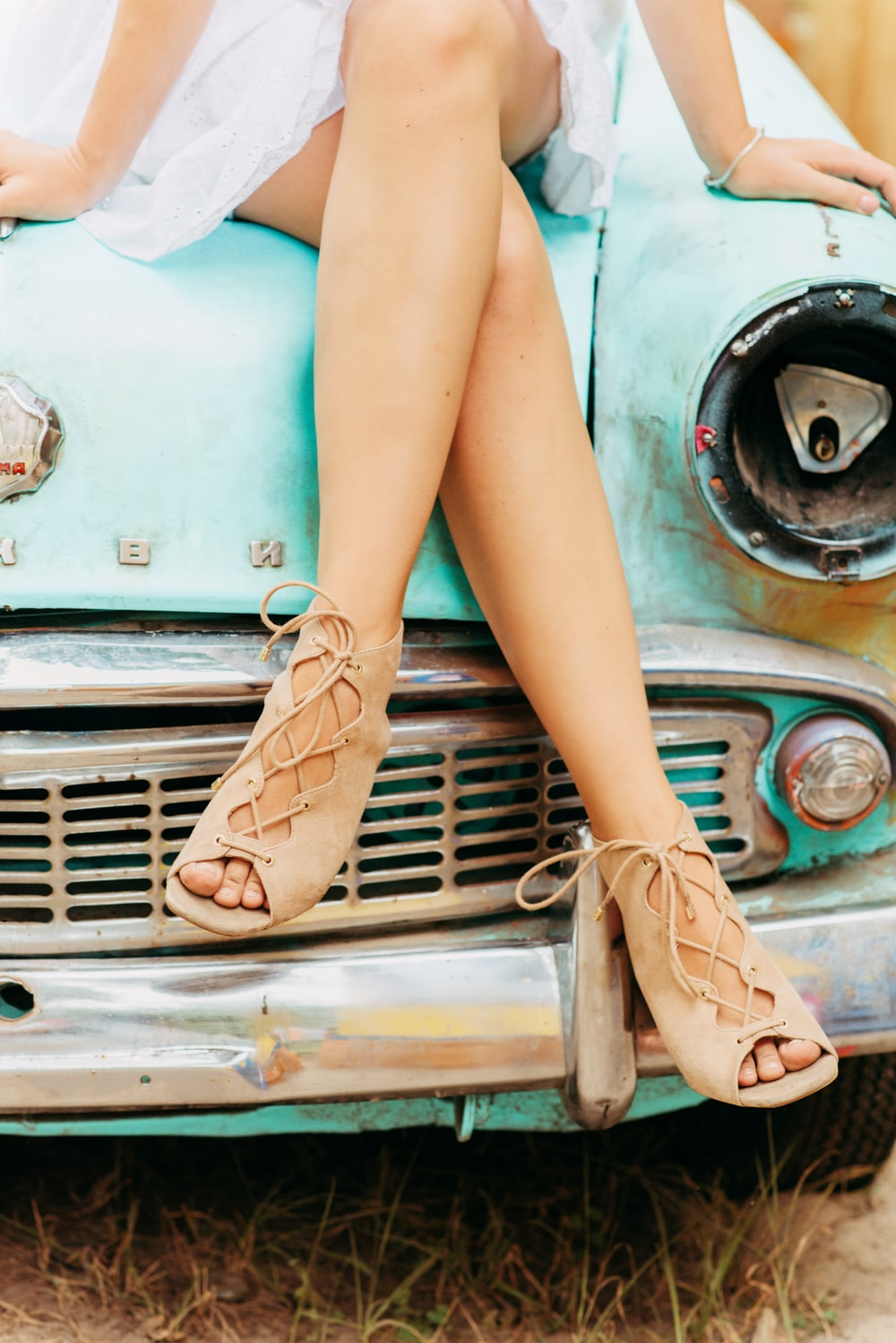 woman in pink leather shoes sitting on teal car
