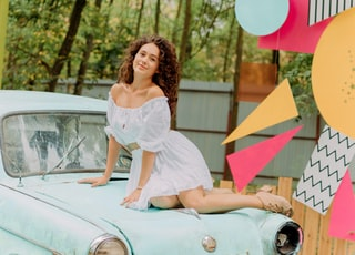 woman in white dress sitting on white car