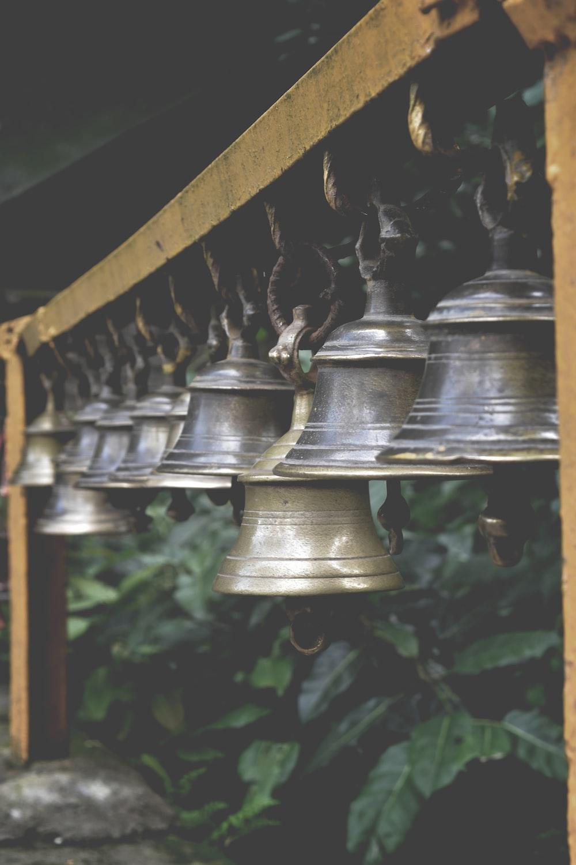 silver bell hanging on black metal bar
