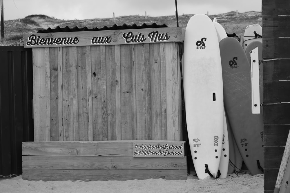 grayscale photo of surfboard on wooden fence