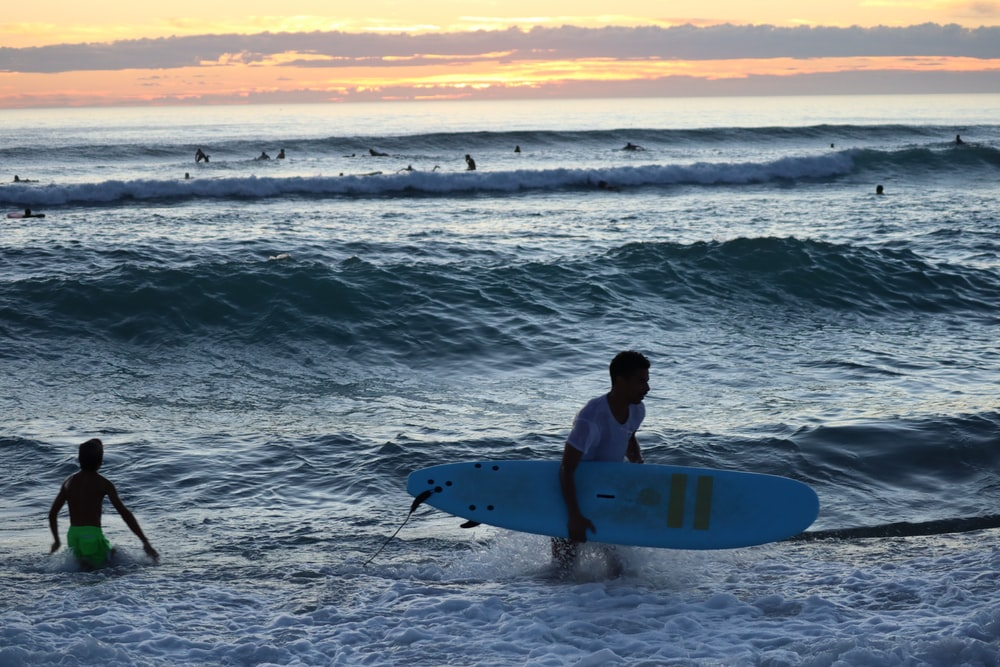 man in white shirt holding white surfboard on beach during daytime