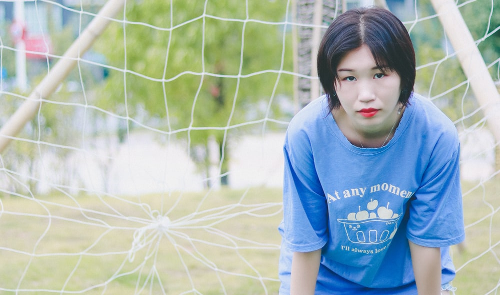 girl in blue crew neck t-shirt standing on green grass field during daytime