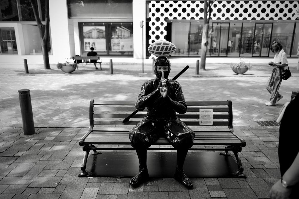 man sitting on bench holding smartphone