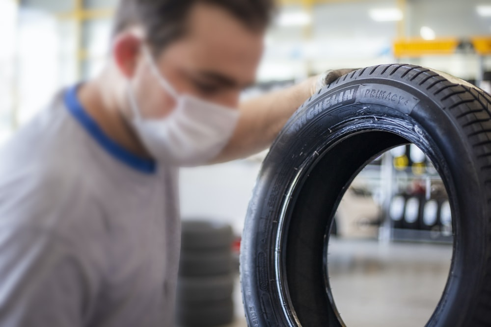man in white shirt holding black tire