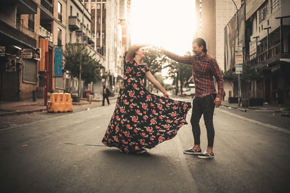 man and woman dancing on street during daytime
