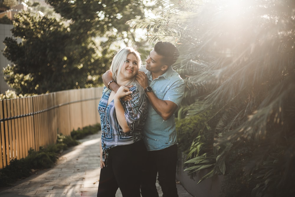 man in gray shirt kissing woman in blue and white shirt