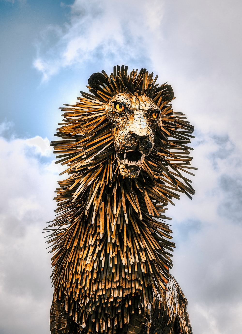 gold and black lion head statue under white clouds and blue sky during daytime