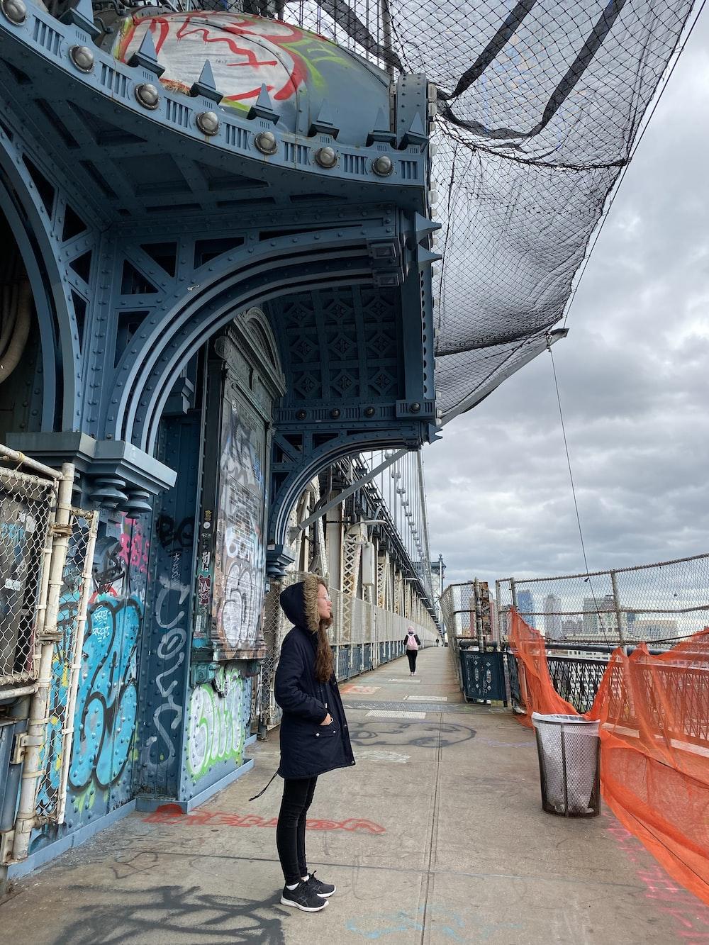 woman in black jacket walking on bridge during daytime
