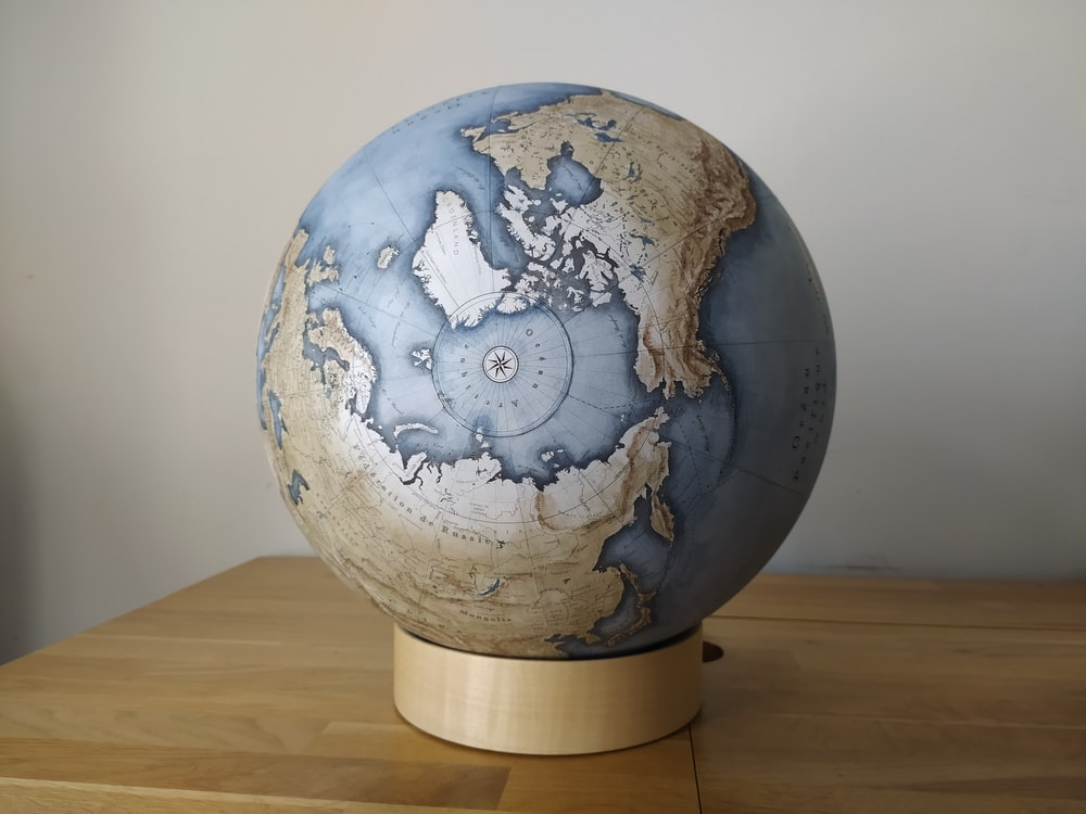 blue and white globe on brown wooden table