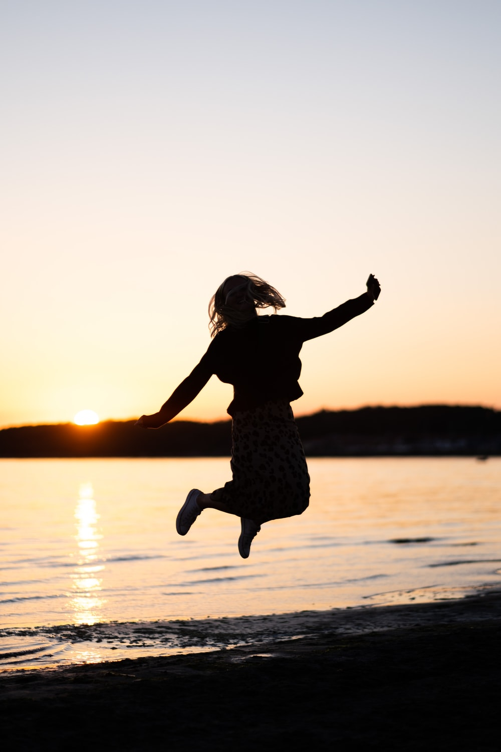 girl in black dress jumping on water during sunset
