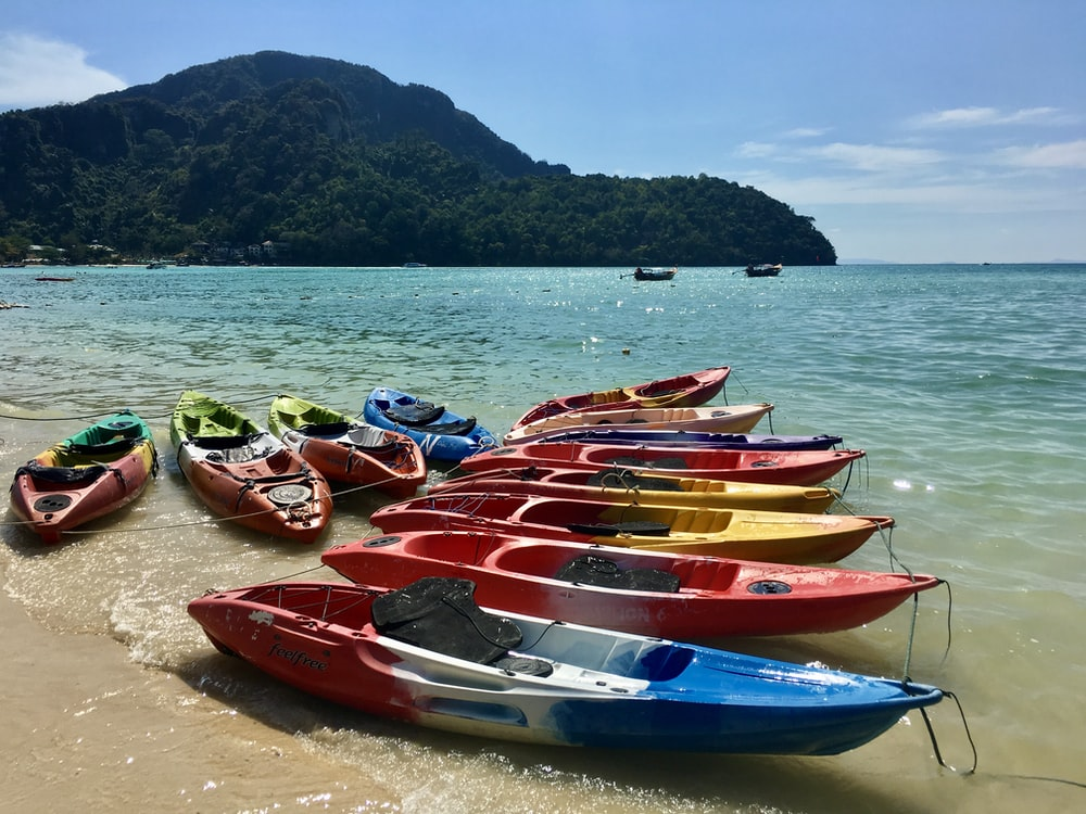 red and blue kayaks on shore during daytime