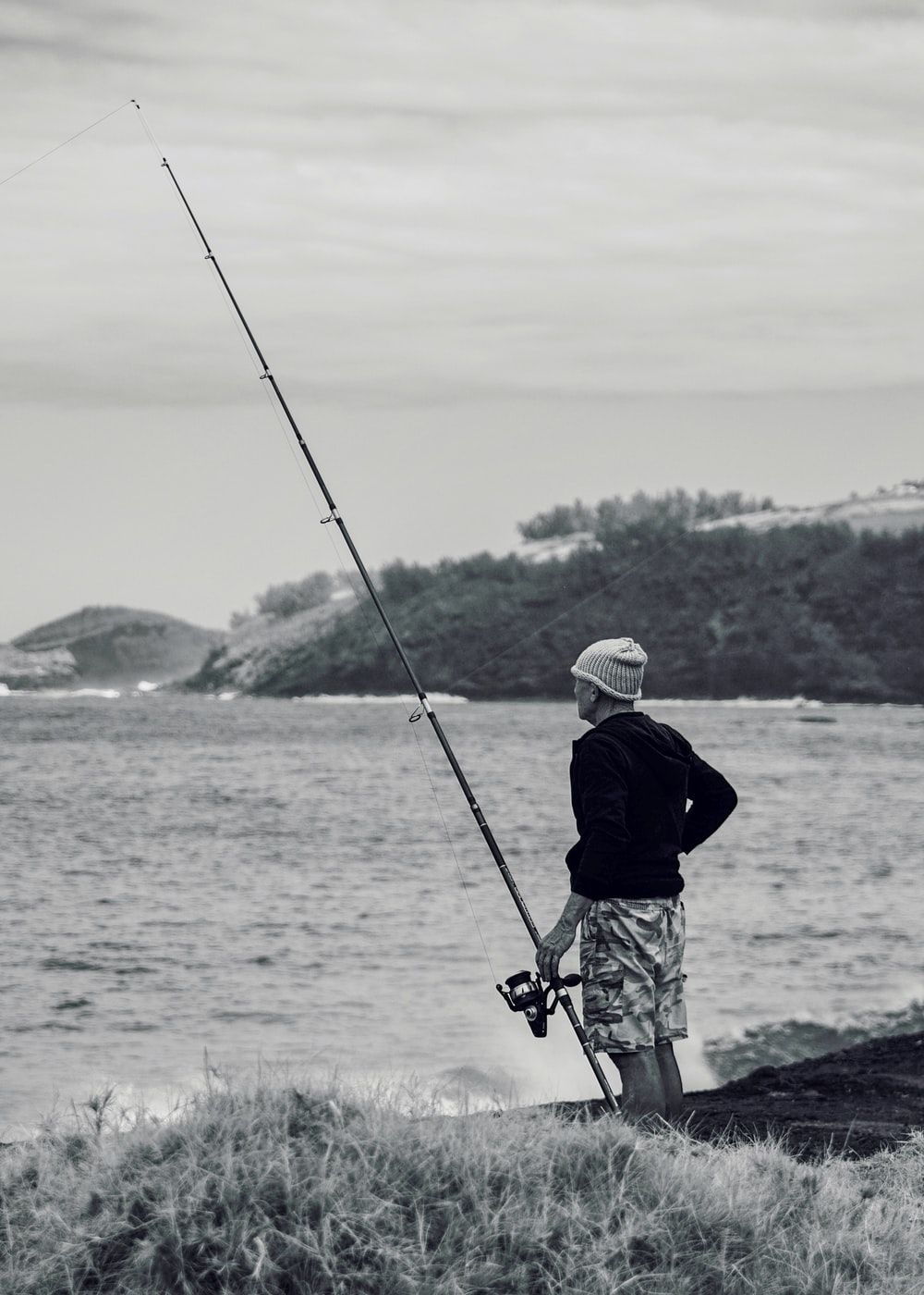 man in black jacket and white helmet fishing on sea during daytime
