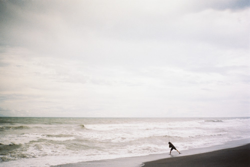 person holding surfboard walking on beach during daytime