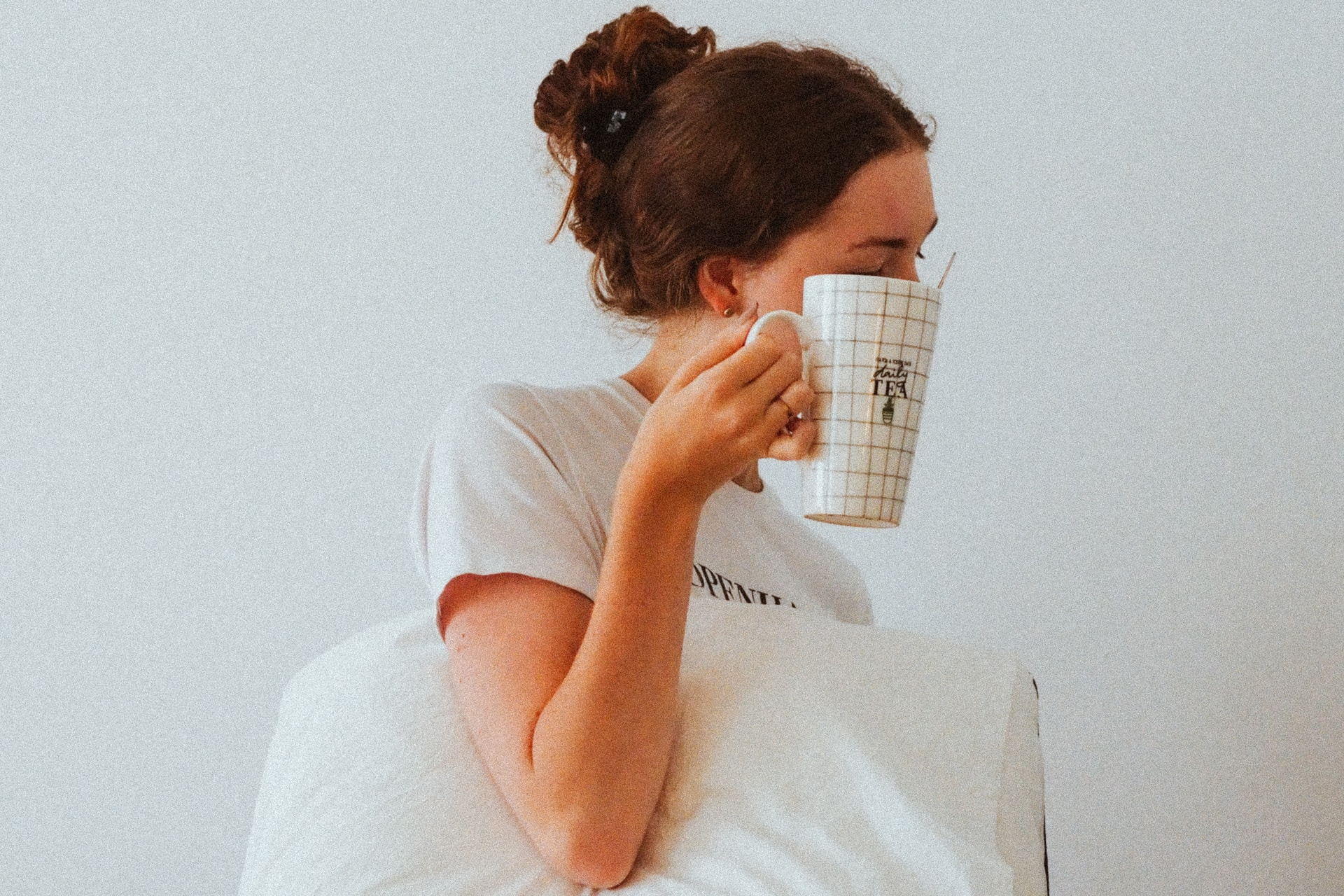 woman in white t-shirt reading book