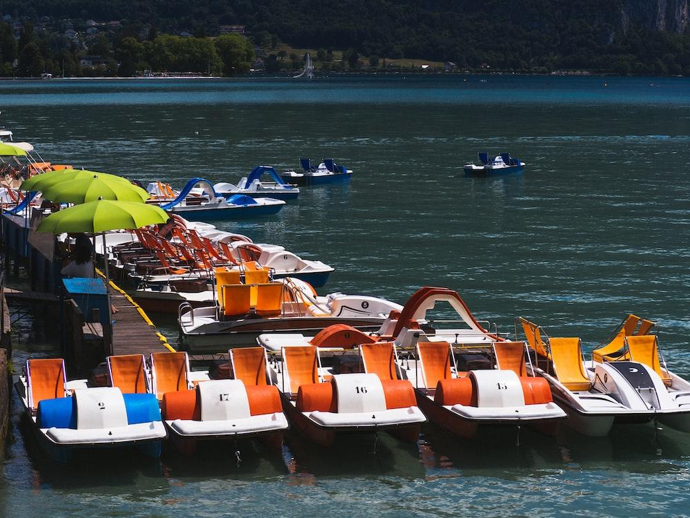 orange and white kayak on sea during daytime