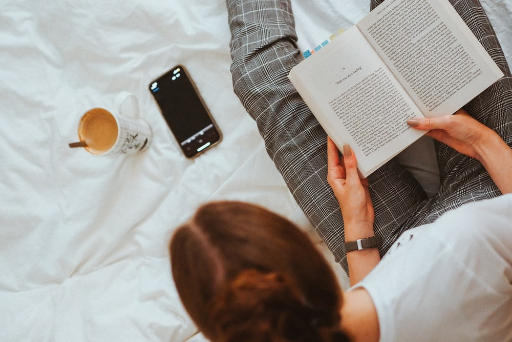 person in white shirt reading book