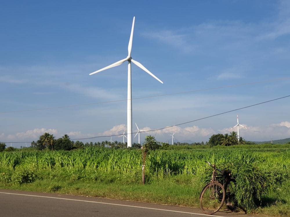 white wind turbine on green grass field under blue sky during daytime