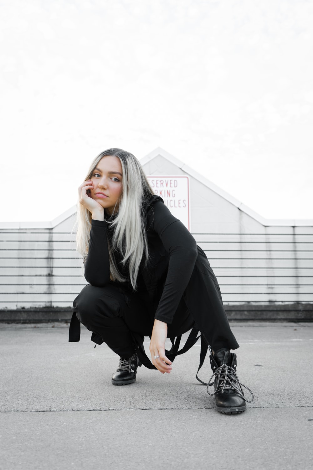 woman in black blazer and black pants sitting on concrete bench during daytime