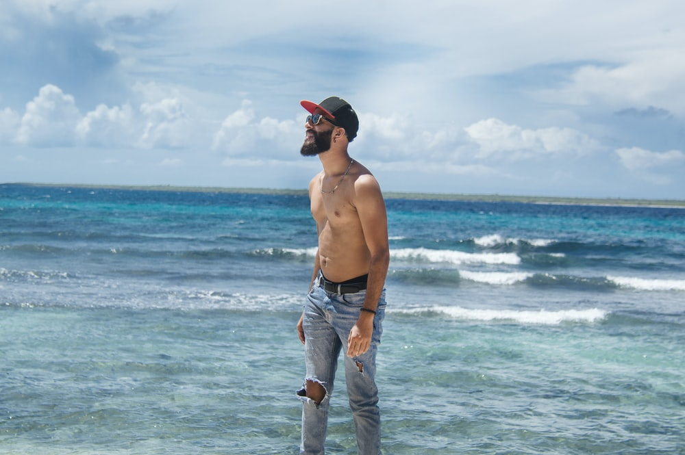topless man in blue denim jeans standing on beach during daytime