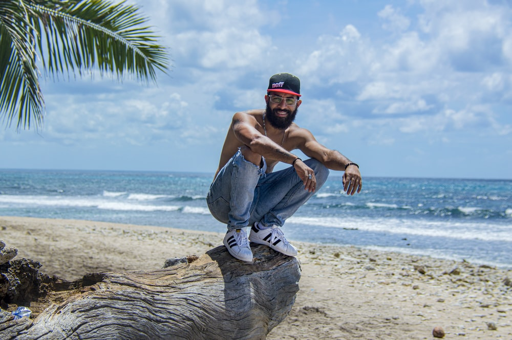 man in blue denim jeans and black cap sitting on tree trunk on beach during daytime