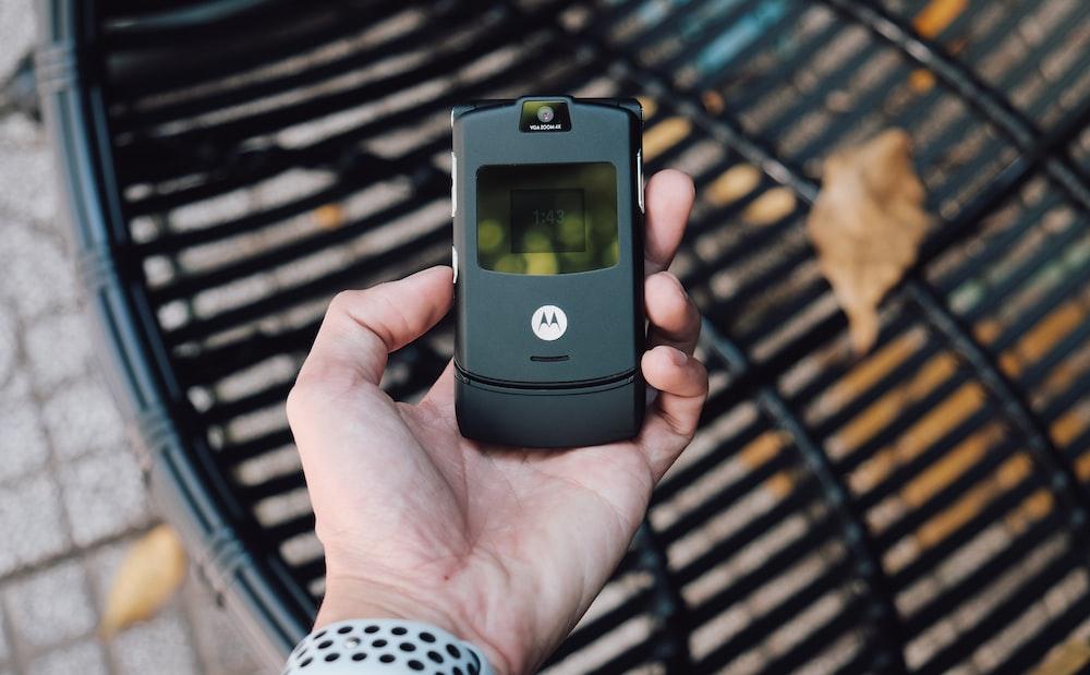 black samsung flip phone on persons hand