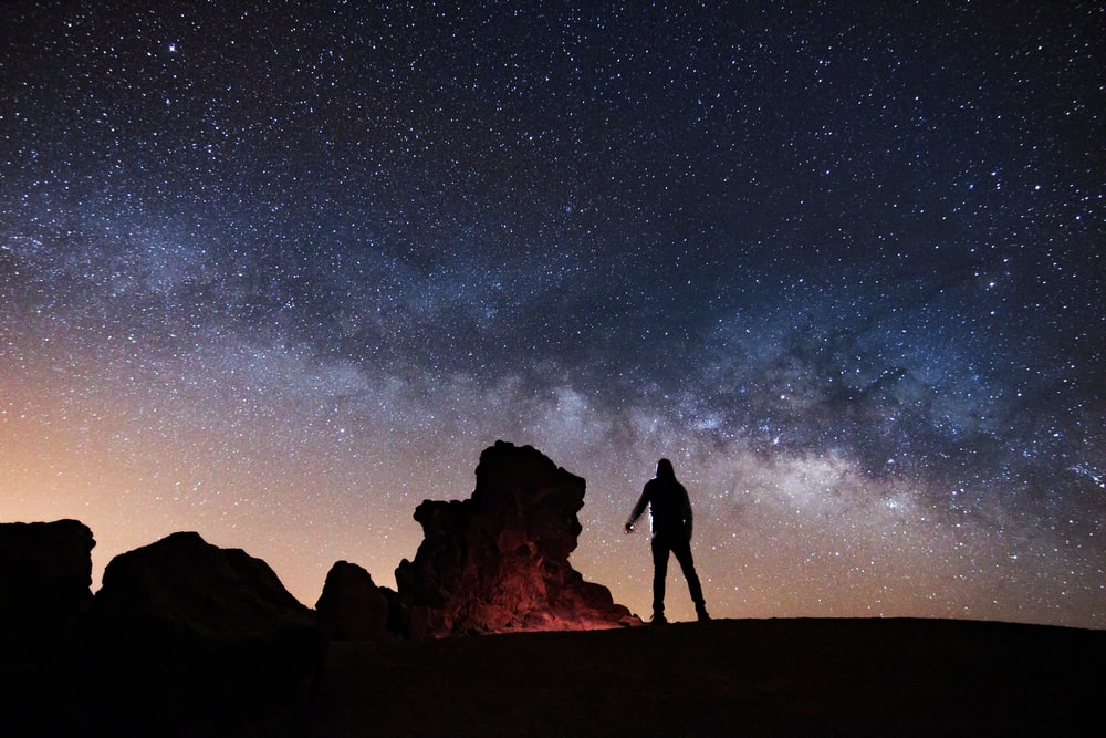 silhouette of man standing on rock formation under starry night