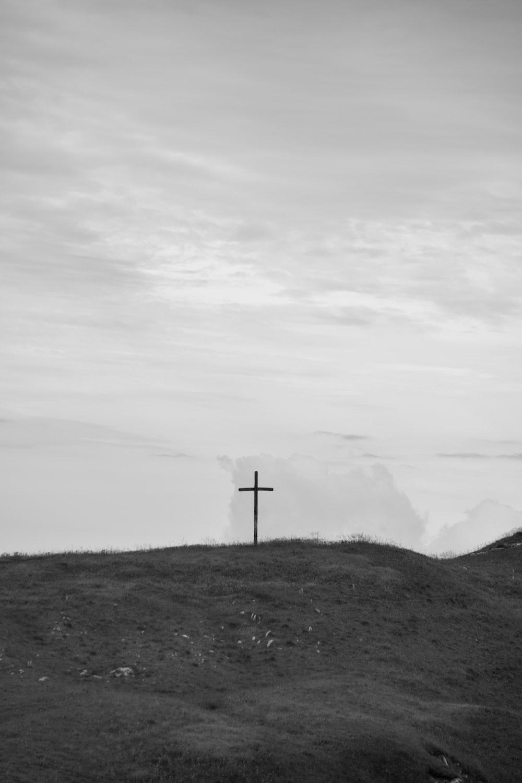 gray cross on green grass field under white sky during daytime