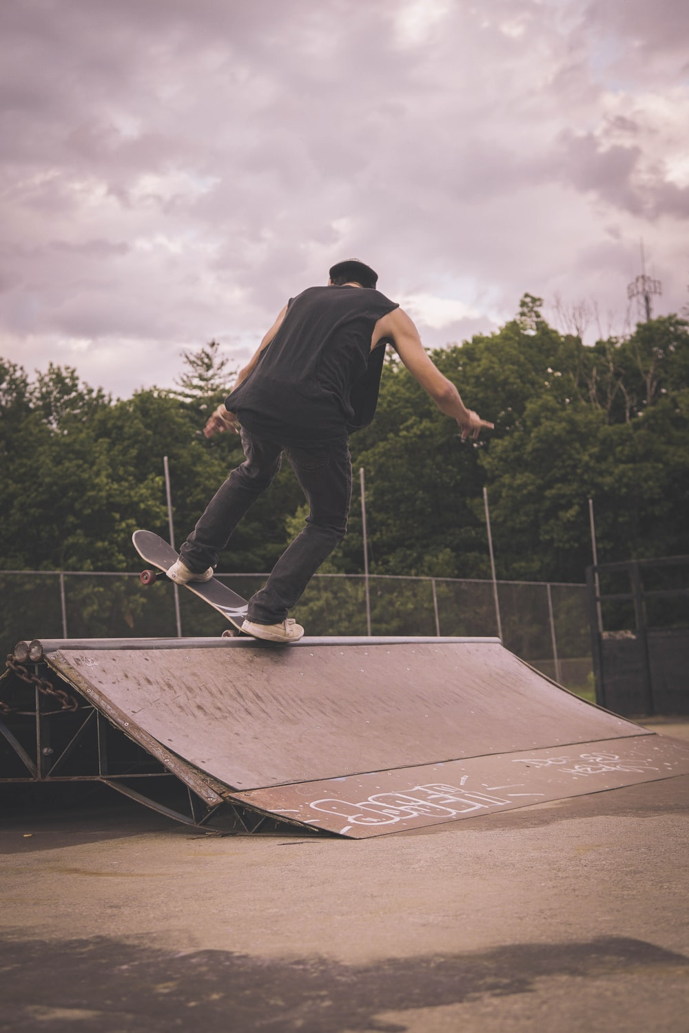 man in black t-shirt and blue denim jeans playing skateboard during daytime