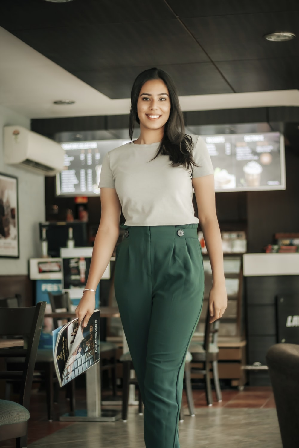 woman in white shirt and green pants standing near black chair