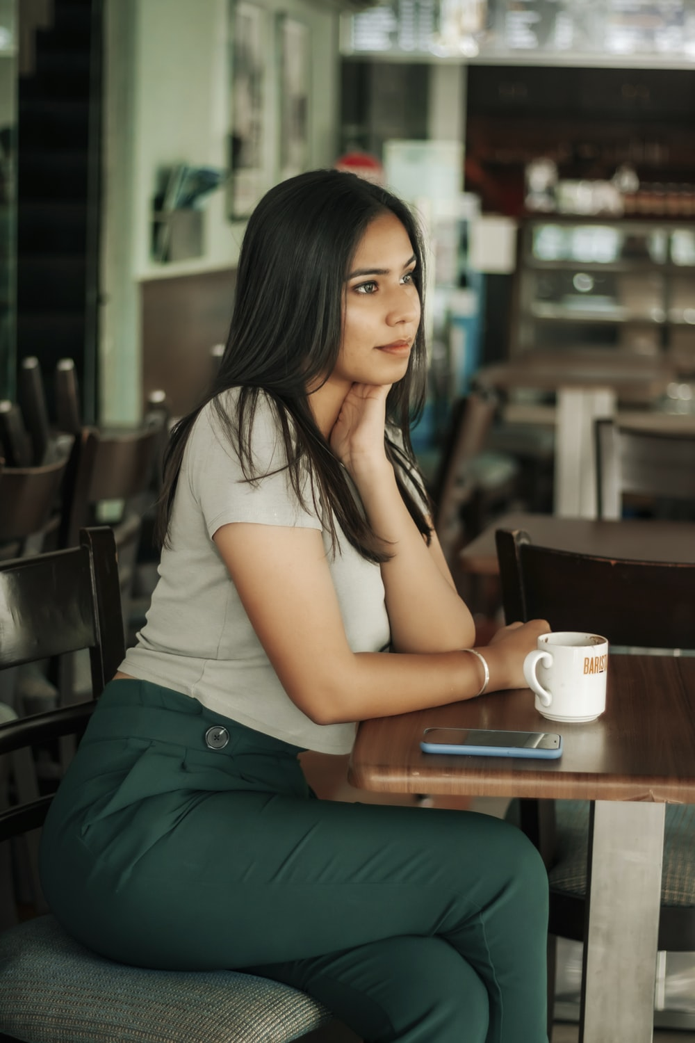 woman in white t-shirt and green skirt sitting on chair holding white ceramic mug