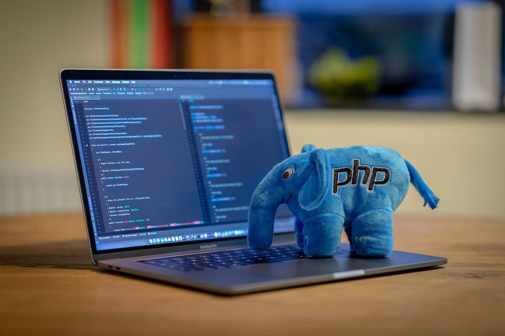 blue and white elephant plush toy on black laptop computer