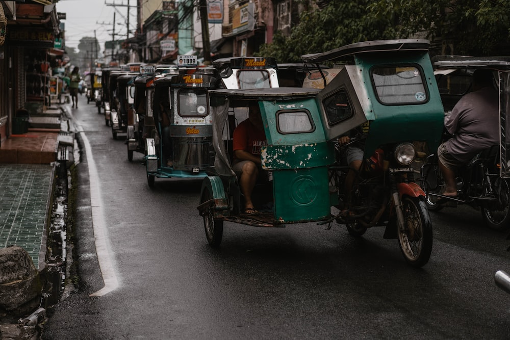 green and black auto rickshaw on road during daytime