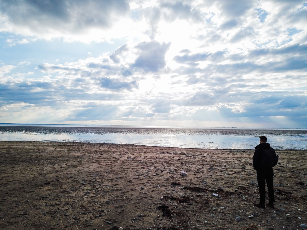 person in black jacket standing on brown sand near sea under white clouds and blue sky