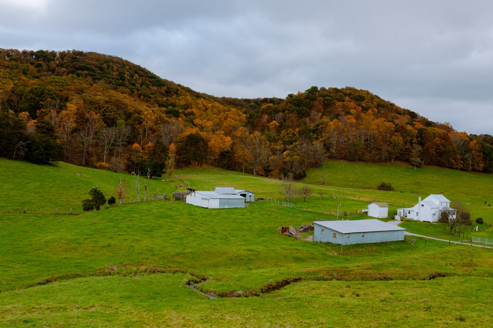 white and brown house on green grass field near mountain under white cloudy sky during daytime