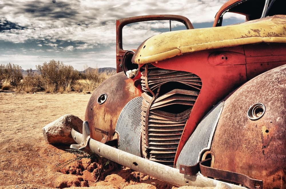 red vintage car on brown soil during daytime