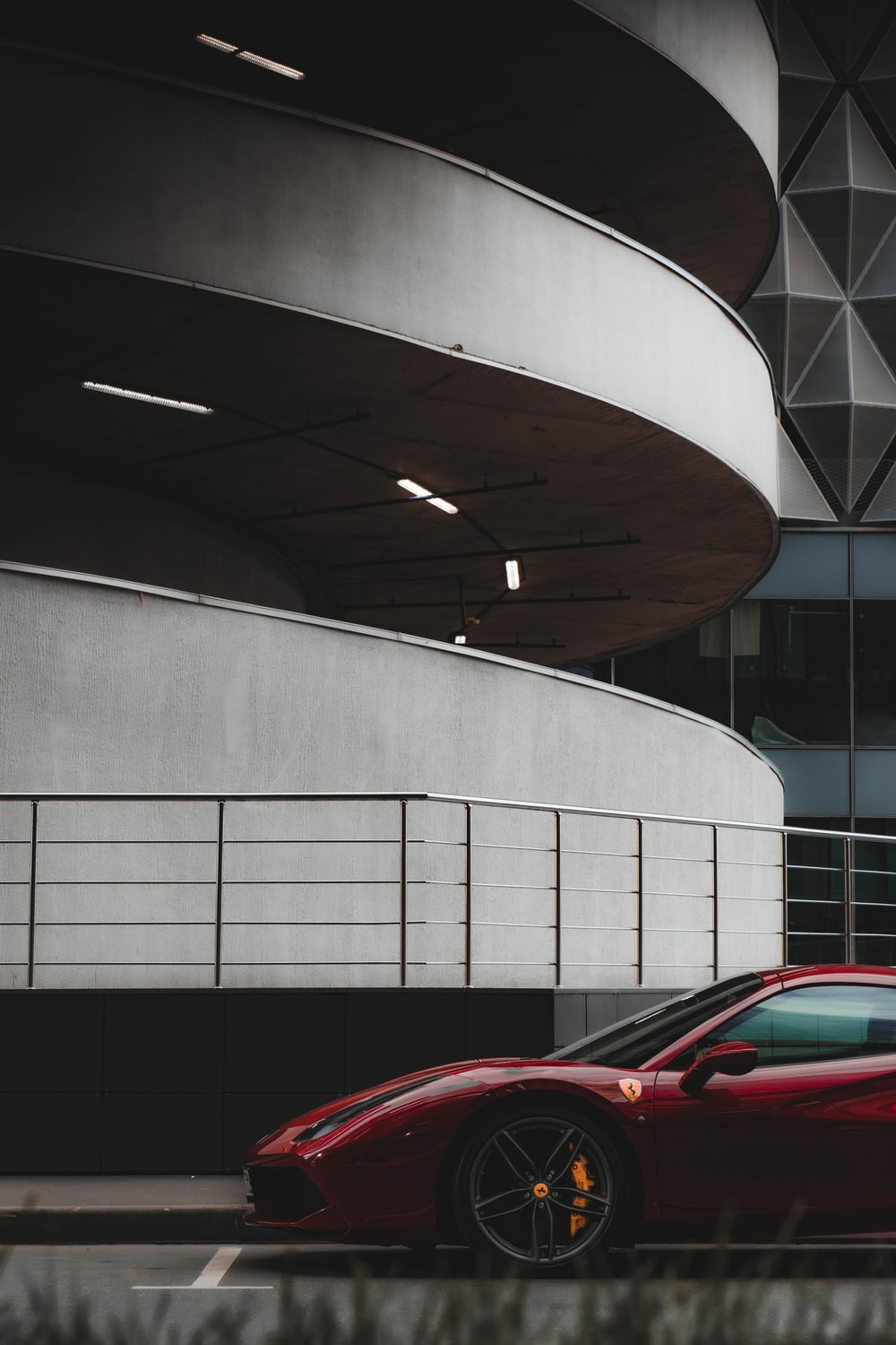 red car parked near white concrete building