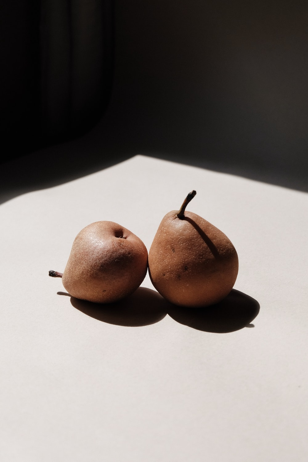 two brown round fruits on white surface