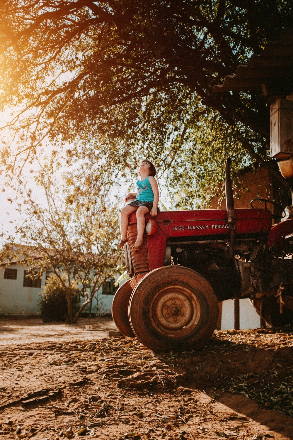 woman in blue denim jeans sitting on red tractor during daytime