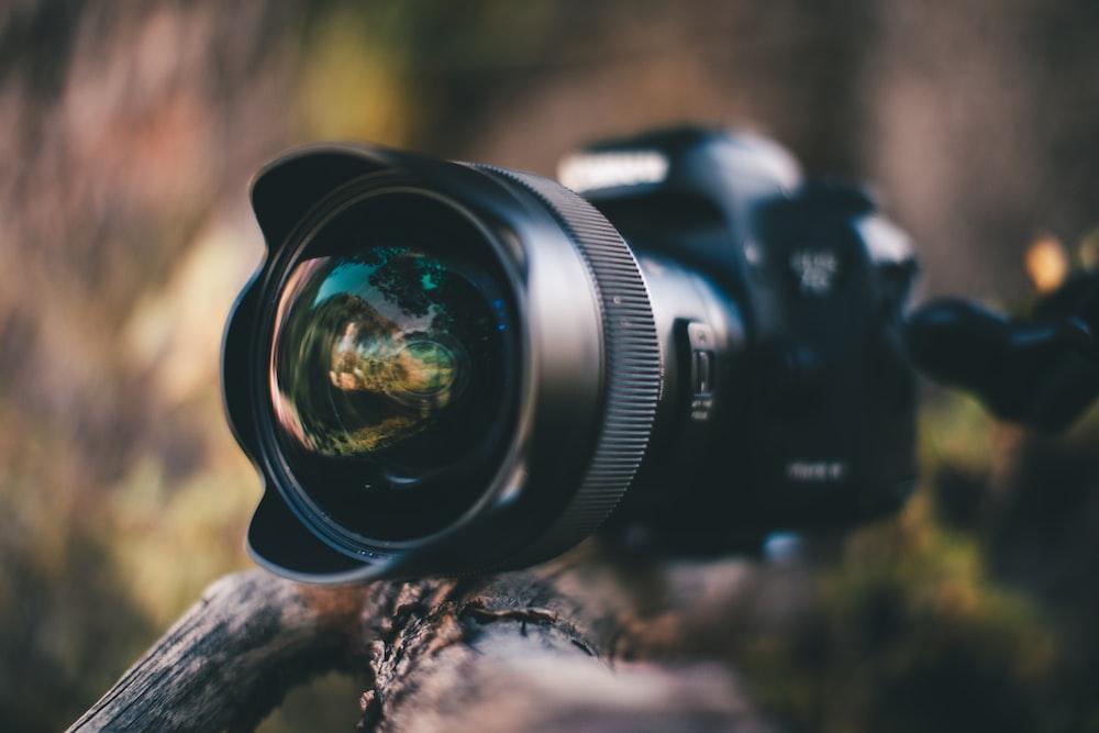 black nikon dslr camera lens on brown wood