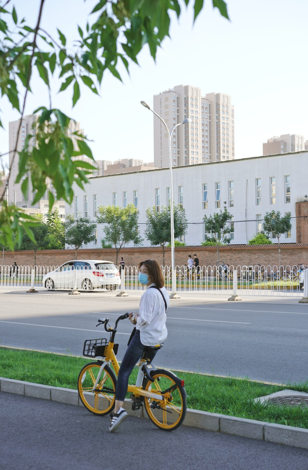woman in white long sleeve shirt riding bicycle on road during daytime