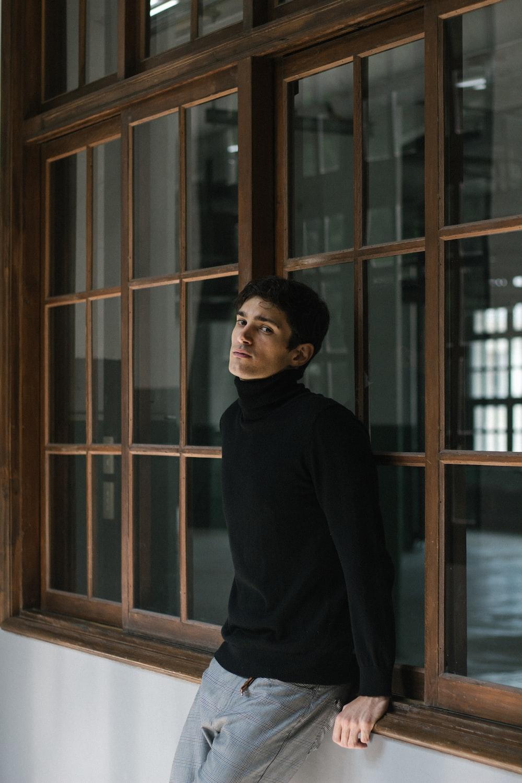 woman in black long sleeve shirt standing beside brown wooden framed glass window