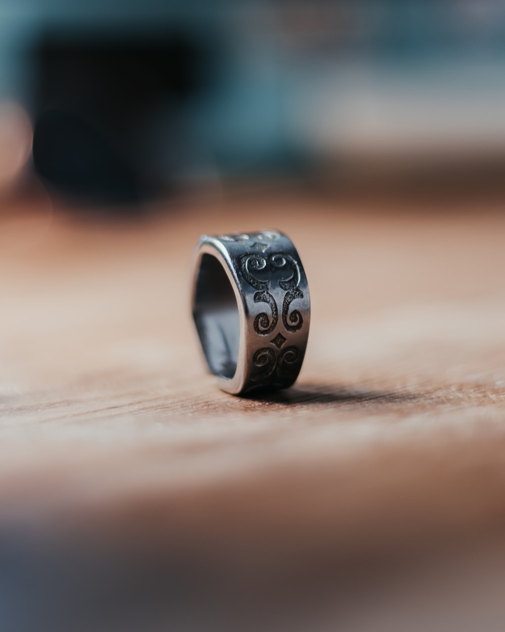 silver and black ring on brown wooden table
