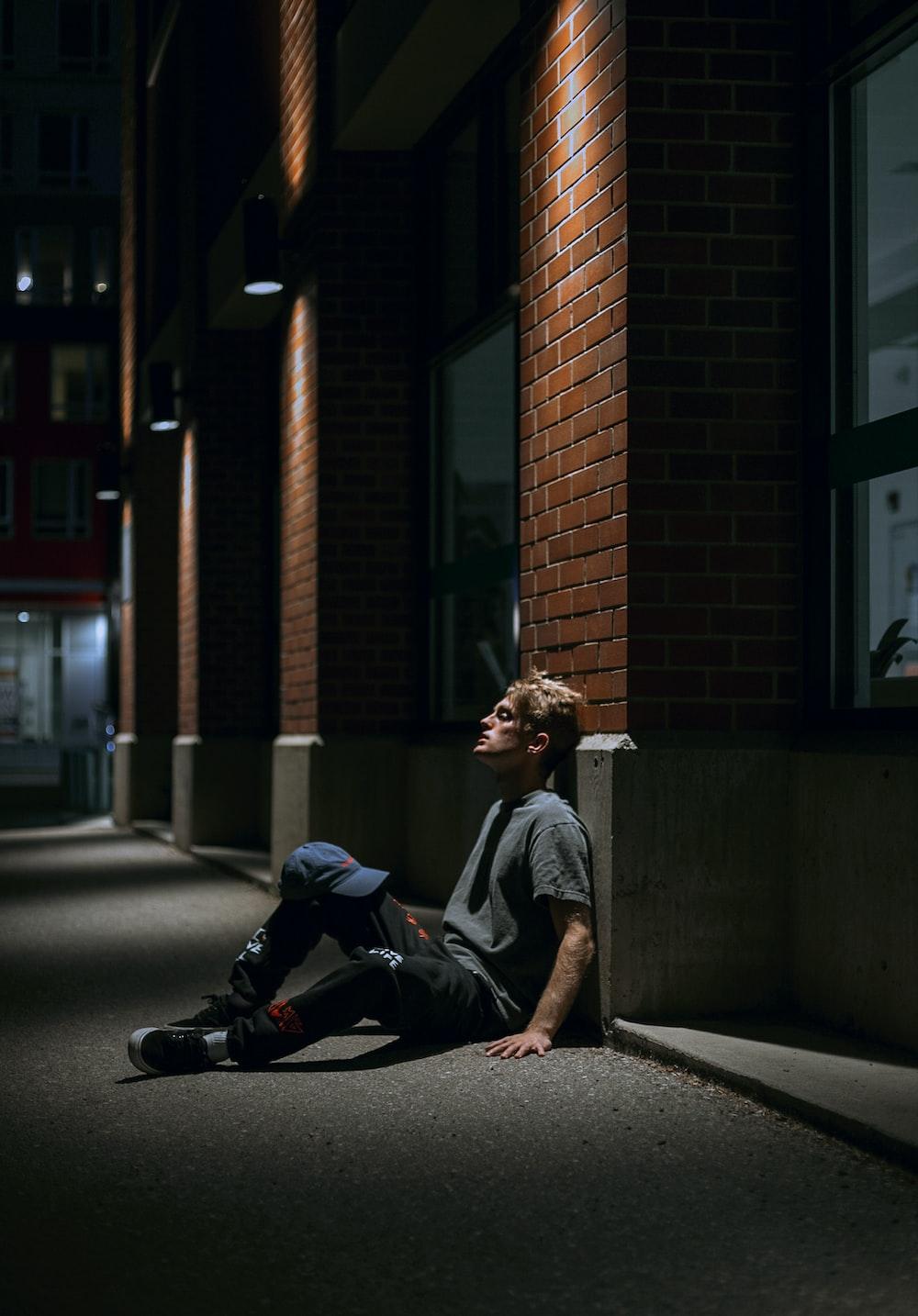 man in gray crew neck t-shirt sitting on sidewalk during daytime