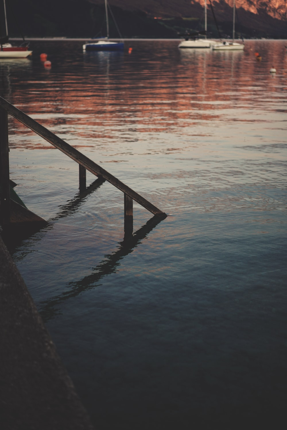 brown wooden dock on body of water during sunset
