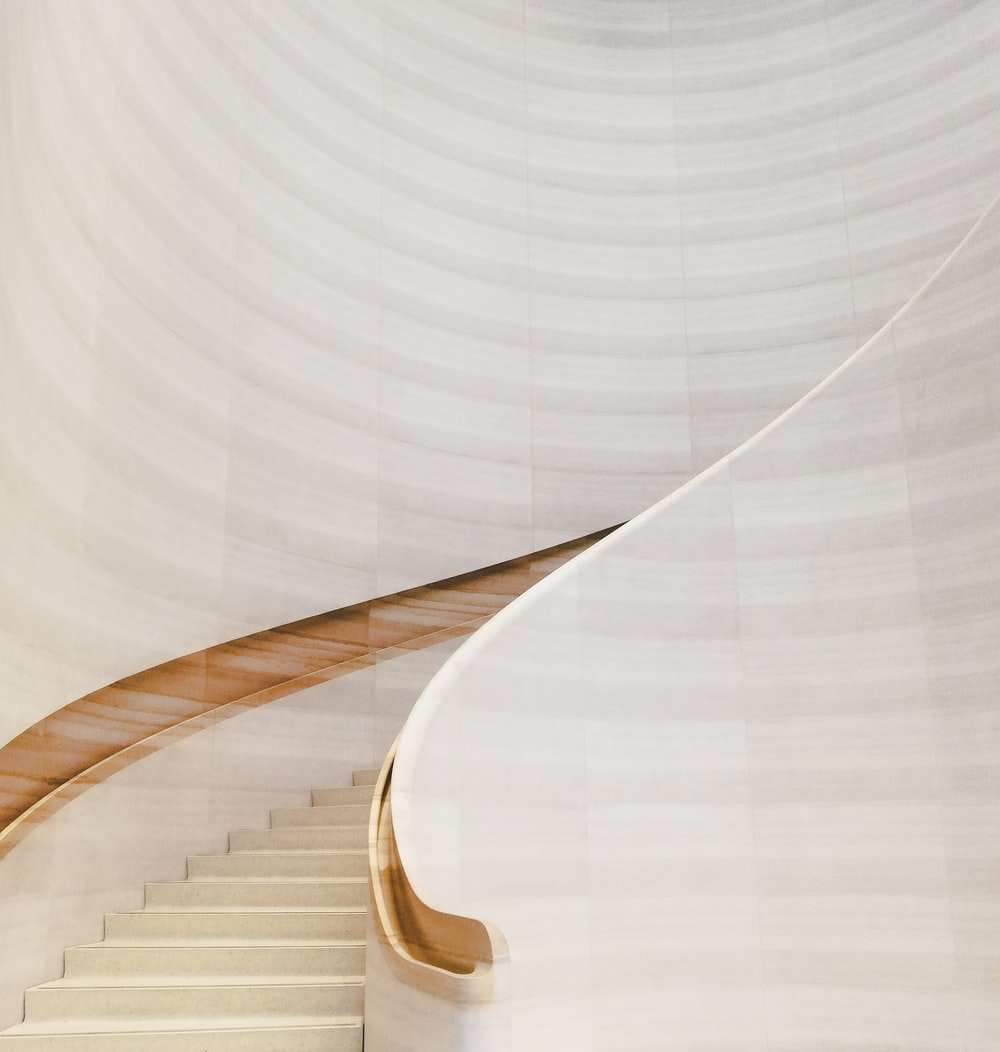 white concrete spiral staircase with brown wooden railings
