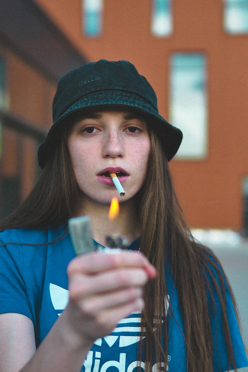 woman in blue shirt holding white disposable cup with lighted cigarette stick