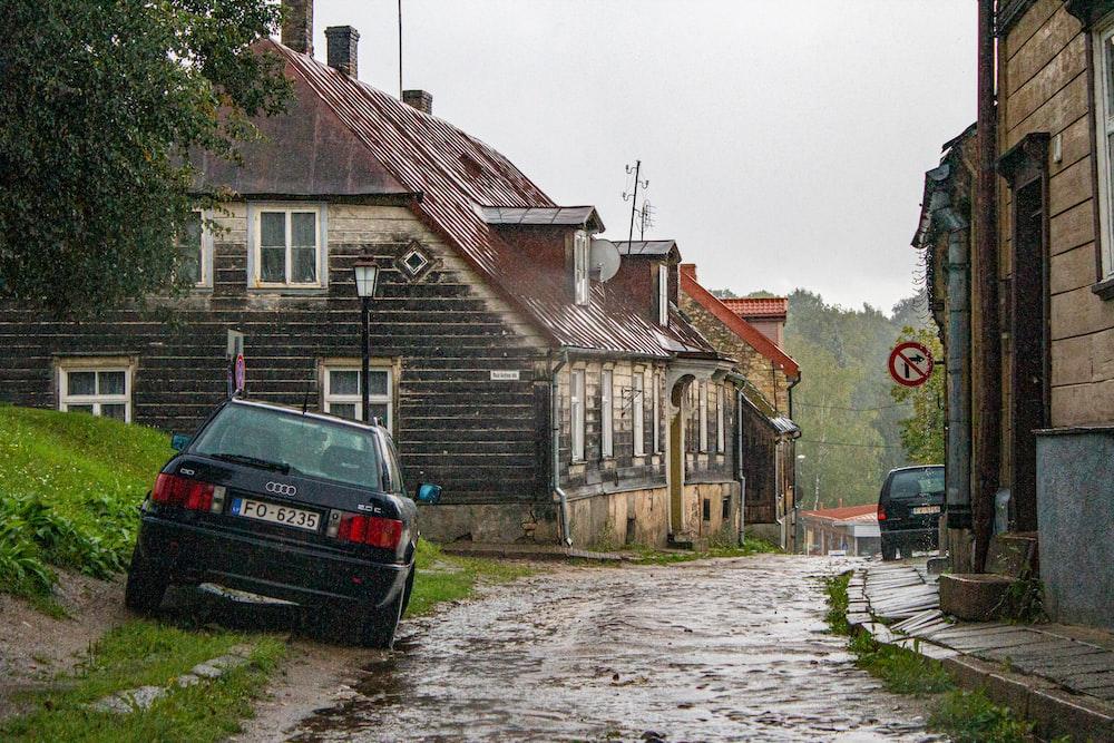 black car parked beside brown brick building during daytime