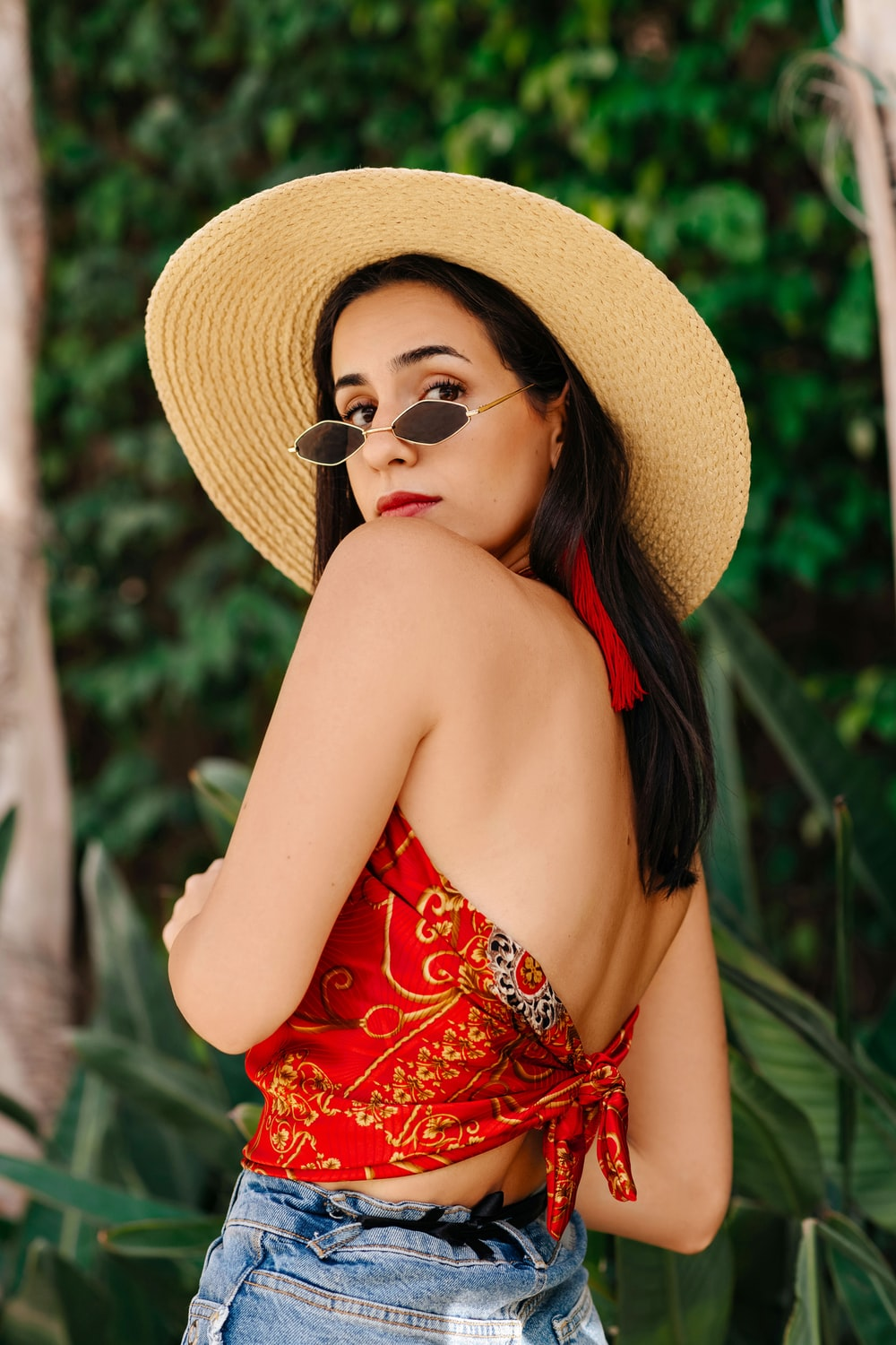 woman in red and white floral tube dress wearing brown sun hat