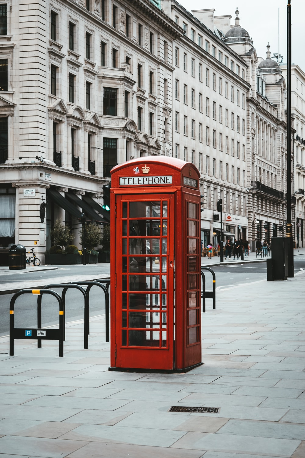 red telephone booth near white concrete building during daytime