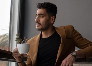 man in brown blazer holding white ceramic mug